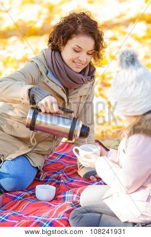 Pleasant mother and daughter drinking tea in park