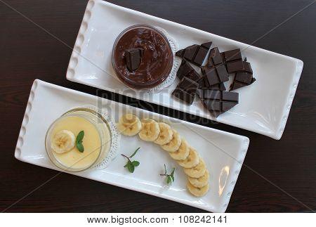 Banana and chocolate pudding with cliced banana, chocolate tiles and m