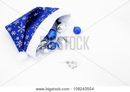 blue hat of Santa Claus and Christmas balls on the snow