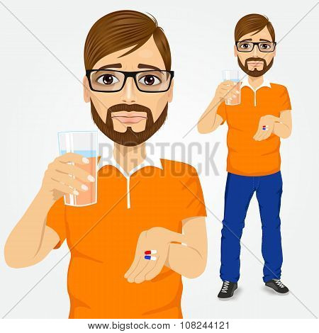 sad man taking pills with glass of water