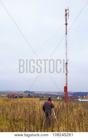 surveyor with a theodolite front of telecommunication tower