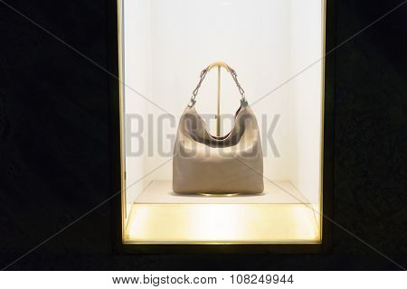 display window against black, fashionable bag in,reflection