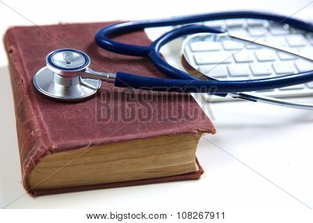 A medical stethoscope near a laptop on table, on white