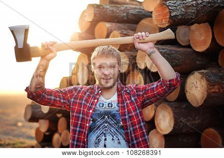 Smiling young bearded lumberjack man carrying an axe on arms