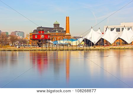 Baltimore waterfront with Seven Foot Knoll Lighthouse at sunset in winter.