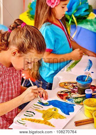 Group little girls painting brush on table in  kindergarten .