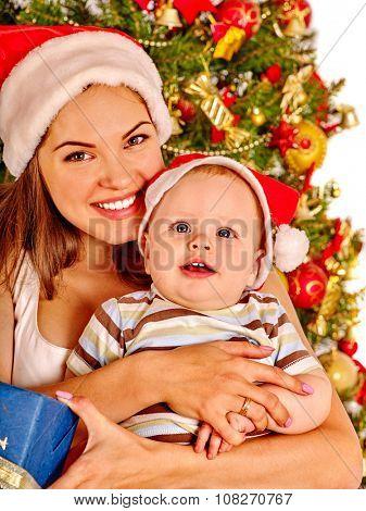 Mom wearing Santa hat gently hugs baby son  under Christmas tree.