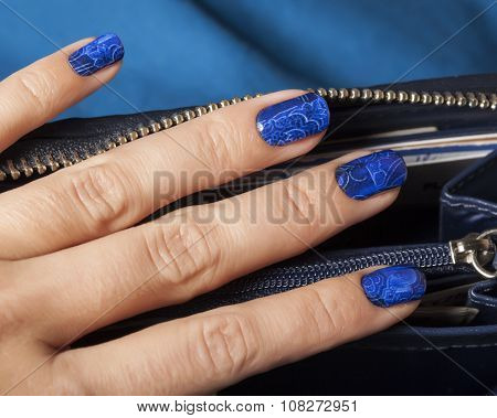 pretty fingers, deep blue manicure close up with purse, luxury design indigo