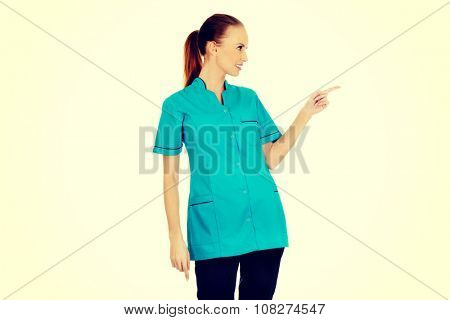 Beautiful female doctor pointing aside.