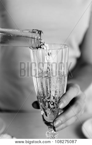 Woman pouring wine into glass,  black and white retro stylization