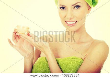 Beautiful woman holding a cream moisturizer.