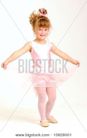 Little young girl wearing pink ballet dress dancing and smile