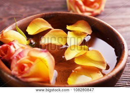 Beautiful orange rose and petals in a bowl of water on wooden background