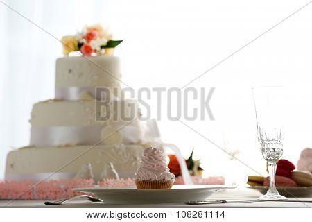 Wedding layered cake in decorated restaurant on window  background