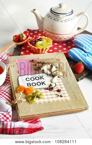 Decorated cookbook with teapot and tasty cake on the table