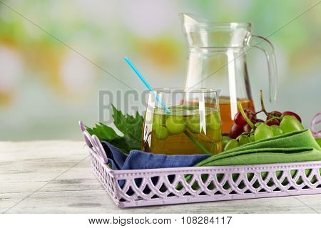Composition of grape, glass and jug with juice on the server