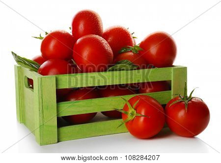 Red tomatoes in green wooden box isolated on white