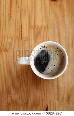Close up overhead view of a cup of strong frothy espresso coffee on a textured wooden surface