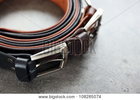 Leather belts with buckles on gray background
