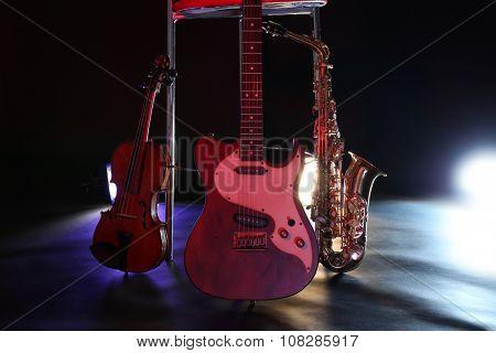 Beautiful golden saxophone and guitar near bar stool on a scene