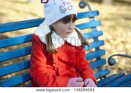 Girl in a coat sitting on the bench