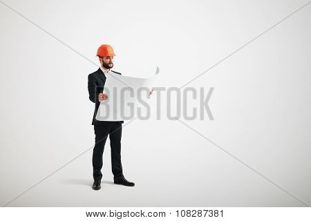 serious businessman in orange hardhat looking at blueprint over light grey background