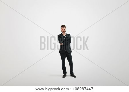 serious thoughtful businessman in formal wear holding his hand at chin and looking down over light grey background