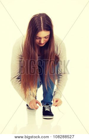 Casual teen woman tie shoes.