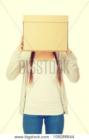 Teen woman covering face with a carton box.