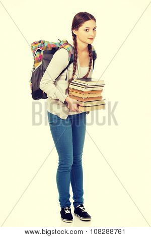 Teenage woman with backpack and heavy books.