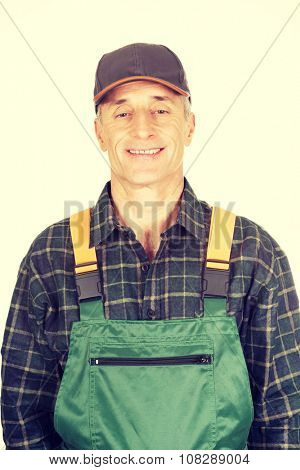 Experienced smiling gardener standing in uniform
