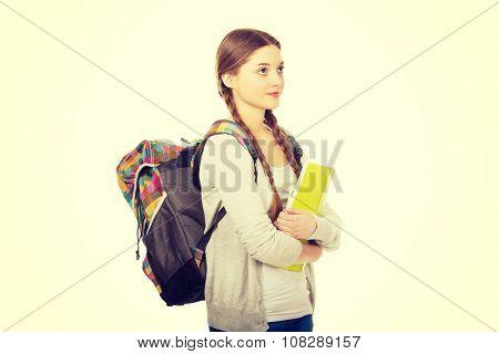 Teenager girl with school backpack holding folder.