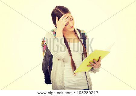 Exhausted teenage girl with school backpack holding folders.
