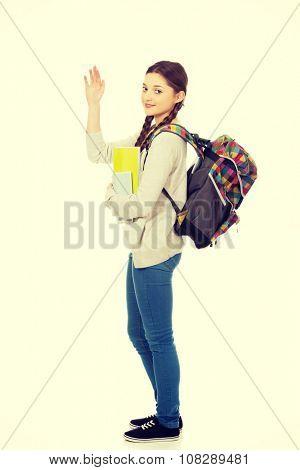 Teenager girl with school backpack waving hand.