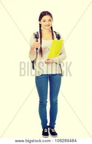 Teenager girl with school backpack and thumbs up.