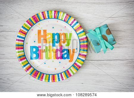 Paper Plates Designed For Birthday Party With Painted Gift Box On The Wooden Background