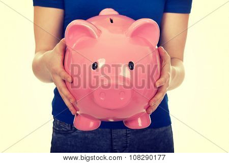 Casual teenage woman holding piggybank.