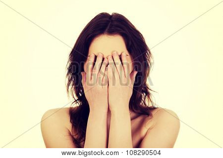 Caucasian woman covering her face.