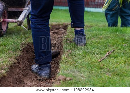 Feet Of Worker Standing On Trench