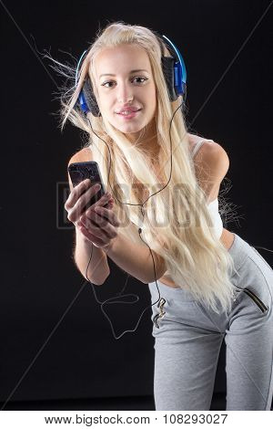Young woman with big blue headphones and mobile phone