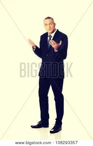 Mature businessman in undecided gesture.