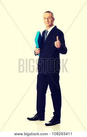 Mature businessman with ok sign holding a binder.
