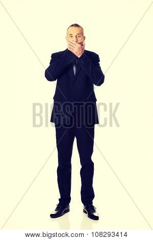 Surprised mature businessman covering his mouth.