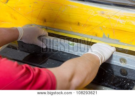 Placing A Spirit Level By Hands Of Handyman On Natural Stone Tile