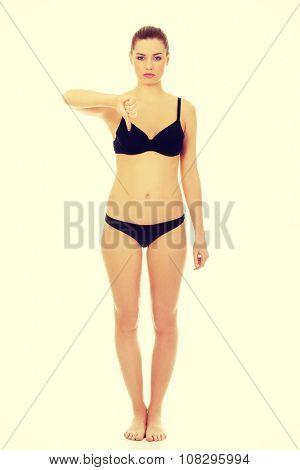 Unhappy woman in bikini showing thumbs down.