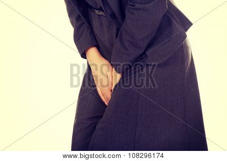 Businesswoman holding her painful crotch.