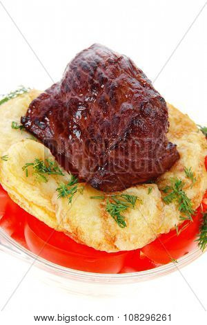 fresh roast beef meat chunk in transparent bowl over baked potatoes and tomatoes served with fill isolated over white background