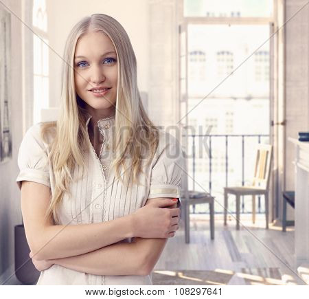 Attractive casual caucasian blue eyed romantic blonde woman at vintage hotel room in Paris. Smiling, daydreaming, standing arms crossed.