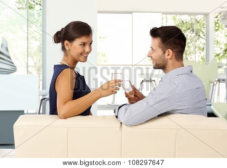 Young caucasian couple sitting at home on sofa clinking champagne glasses. Smiling, eye contact, romance.