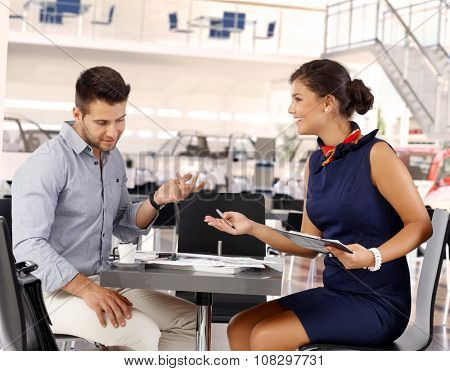 Happy attractive caucasian businesswoman representative with male client at car saloon reviewing business papers. Sitting at coffee table, gesturing. Smiling, wearing dress.